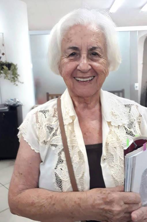 mulher branca idosa sorri segurando livros e cadernos nos braços