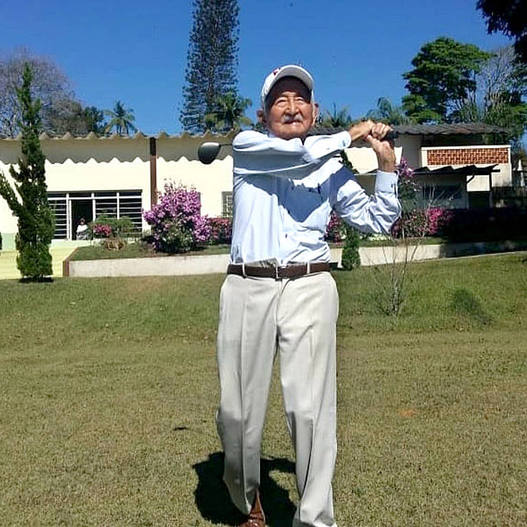homem idoso joga golfe em campo ensolarado e florido