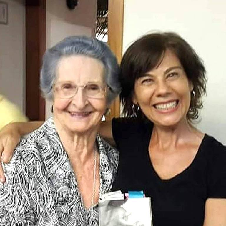 uma mulher idosa de cabelos grisalhos abraça uma mulher mais jovem de cabelos acaju, as duas sorriem para a câmera