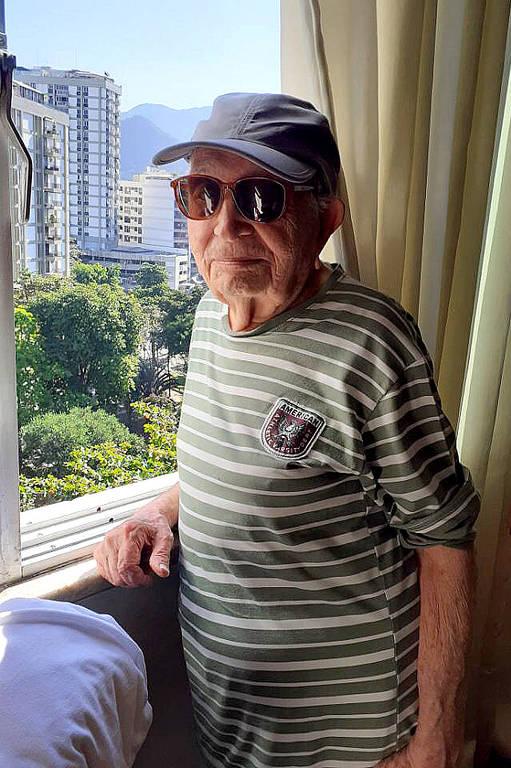 homem idoso se apoia no batente da janela. ele usa boné e óculos de sol