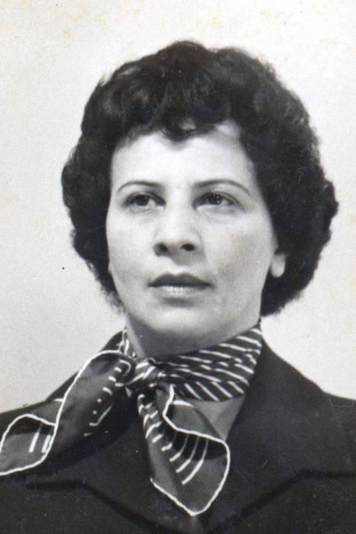 retrato em preto e branco de jovem mulher negra trajando terno e lenço enrolado no pescoço