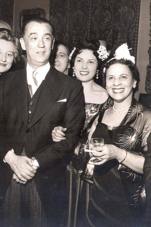 mulher parda usa vestido elegante e está de braço dado com homem branco de terno; os dois estão sorrindo e rodeados de pessoas em um elegante saguão