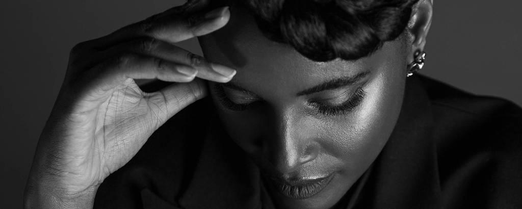 Mulher negra olha para baixo e apoia mão em cima do cabelo em foto preto e branco