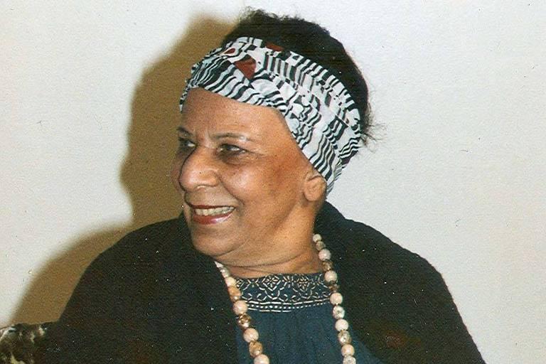 mulher idosa sentada veste casaco preto e vestido azul, ela usa um lenço estampado amarrado nos cabelos e olha para o lado sorrindo