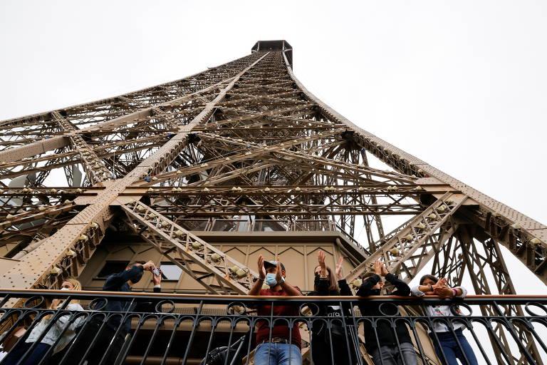 Turistas batem palma em cima da Torre Eiffel, vistos de baixo.