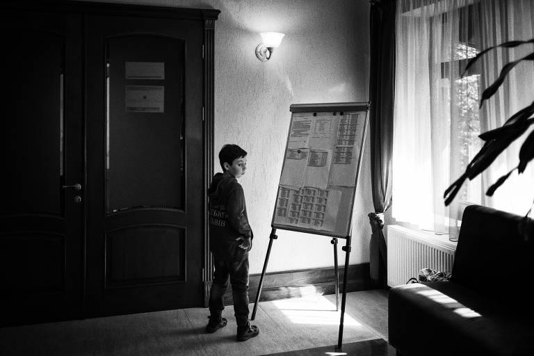 Criança olha placar de jogo anotado em papel