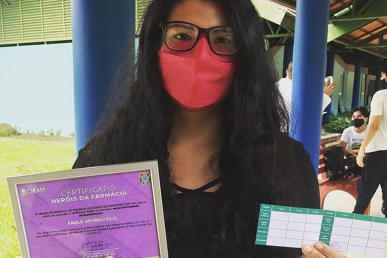 Deborah Muniz posa para foto comemorando com seu cartão de vacinação e um certificado em homenagem ao pai, vítima da Covid (Foto: Arquivo Pessoal )