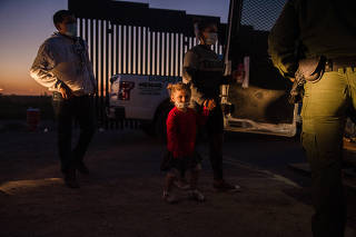 A young girl being transported to an immigrant processing center by U.S. Border Patrol agents in Yuma, Ariz. on May 4, 2021. (Ariana Drehsler/The New York Times)
