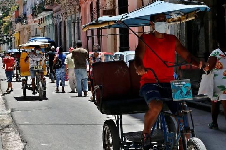 Pedestres e bici-taxis passam por rua em Cuba