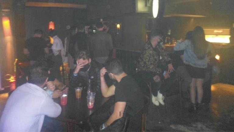 Dezenas de pessoas aparecem em um bar, algumas cobrem o rosto