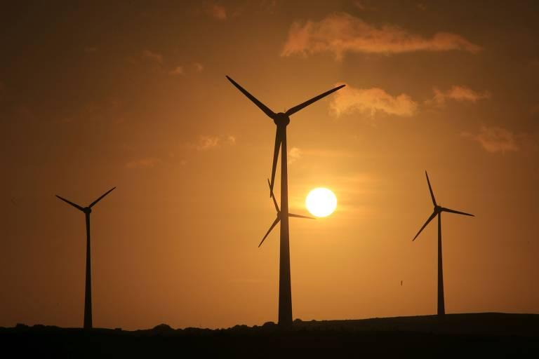 Turbinas eólicas com o sol se pondo ao fundo