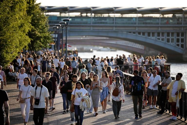 Pessoas passeiam à beira do rio Tâmisa, em Londres, na última sexta (16)