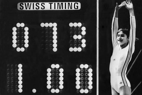 (FILES) In this file photo taken on July 19, 1976 Romanian champion Nadia Comaneci, aged 14, jubilates when scoreboard shows the perfect score of 10 during Olympic Games 19 July 1976 in Montreal after her acrobatic compulsory at uneven bars. She was awarded with ten points in two exercices and captured 3 gold medals (beam, uneven bars and general competition). Legendary gymnast, during her career Nadia Comaneci captured four Olympic gold medals (1976 : beam, uneven bars and general competition - 1980, beam) and was the first to score 10 in her discipline. - The 32nd Summer Olympics finally start on July 23, 2021, in Tokyo after a year's delay because of the coronavirus pandemic. (Photo by - / AFP) ORG XMIT: DOC2 ORG XMIT: AGEN2106212106049384