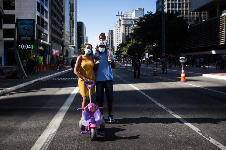 A executiva de vendas Caroline de Oliveira Rivelles ao lado do marido, o motoboy Ernande de Almeida Jesus, e da filha, Lorena