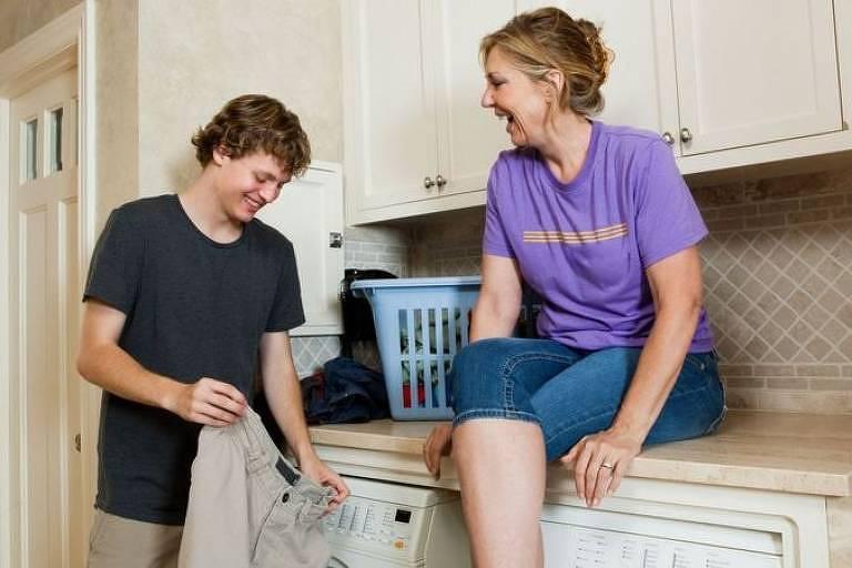 Adolescente branco rindo e colocando roupas para lavar ao lado da mãe sentada em um balcão e rindo
