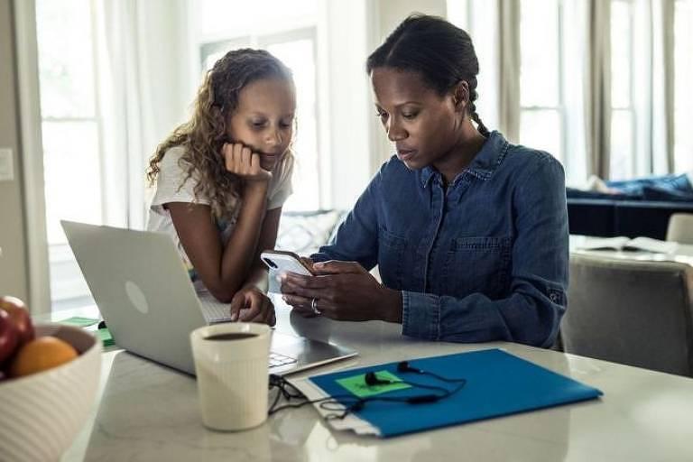 Mulher negra usando celular e computador com filha ao lado