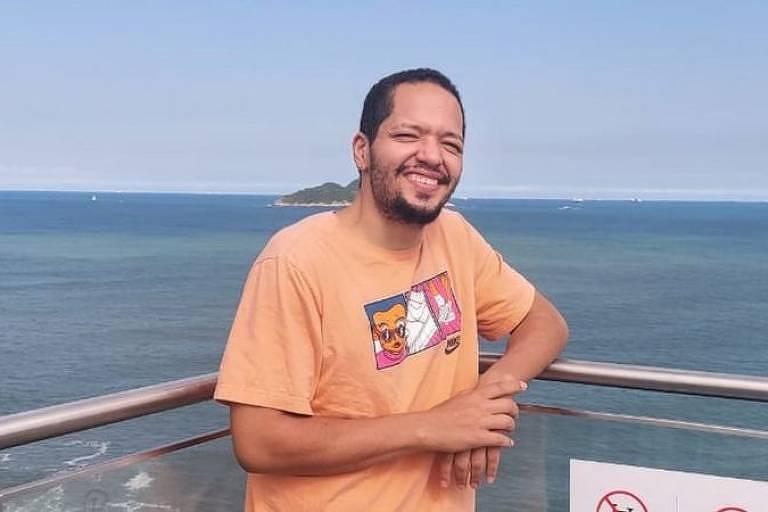 Homem negro de camiseta laranja sorrindo em frente a uma praia