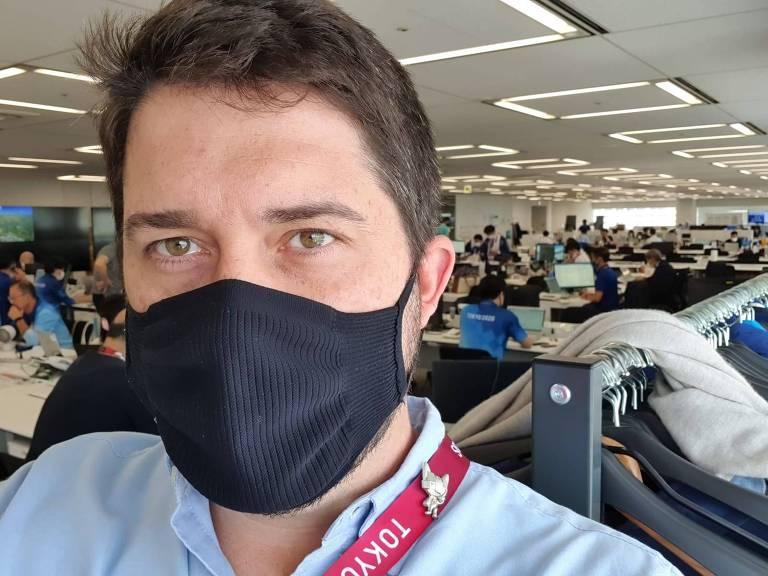 Homem de máscara e camisa faz selfie com pessoas trabalhando em escritório atrás