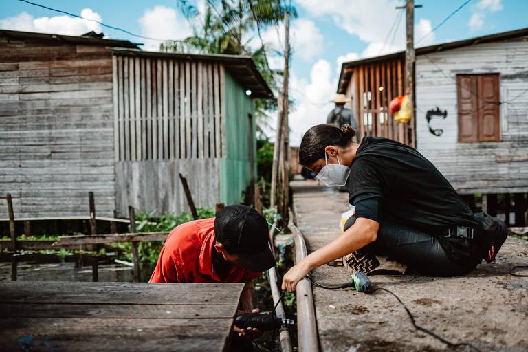 mulher de roupa preta está sobre passarela e homem de roupa laranja abaixo dela, examinando uma tubulação com casas de madeira ao redor