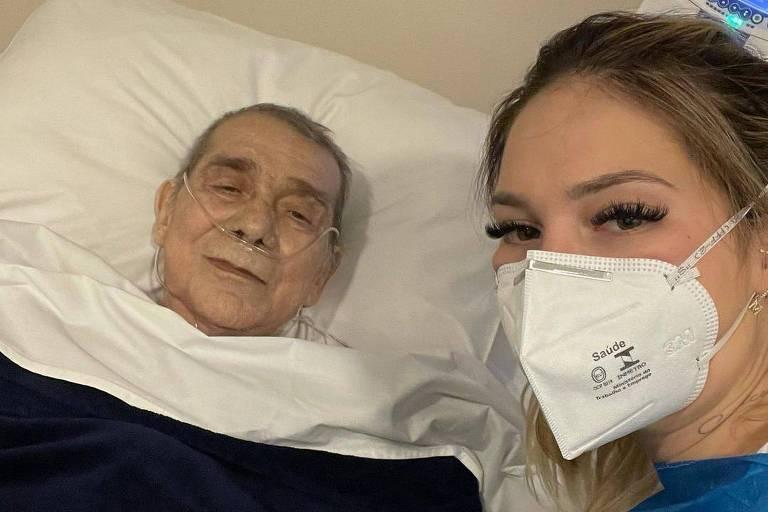 Homem deitado em cama de hospital com tubos de respiração e mulher loira usando máscara e avental azul