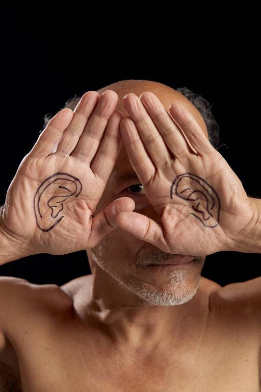 Homem posiciona as mãos em frente ao rosto, e vê-se desenhado nas palmas de suas mãos duas orelhas