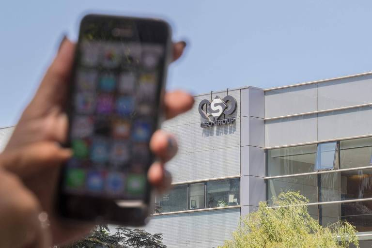 Na foto, uma mulher usa seu iPhone em frente ao prédio da empresa israelense NSO, responsável pelo Pegasus, ferramenta espiã que invade dispositivos sem necessidade de cliques em links ou arquivos.