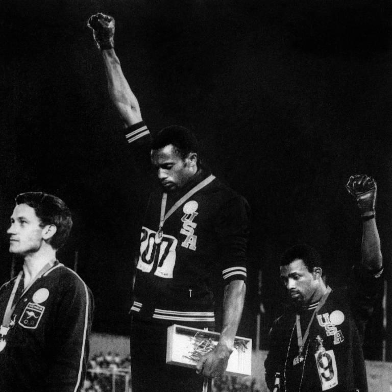 Tommie Smith (acima) e John Carlos (à dir.) erguem seus punhos com a luva preta dos Panteras Negras para protestar contra a segregação racial os EUA