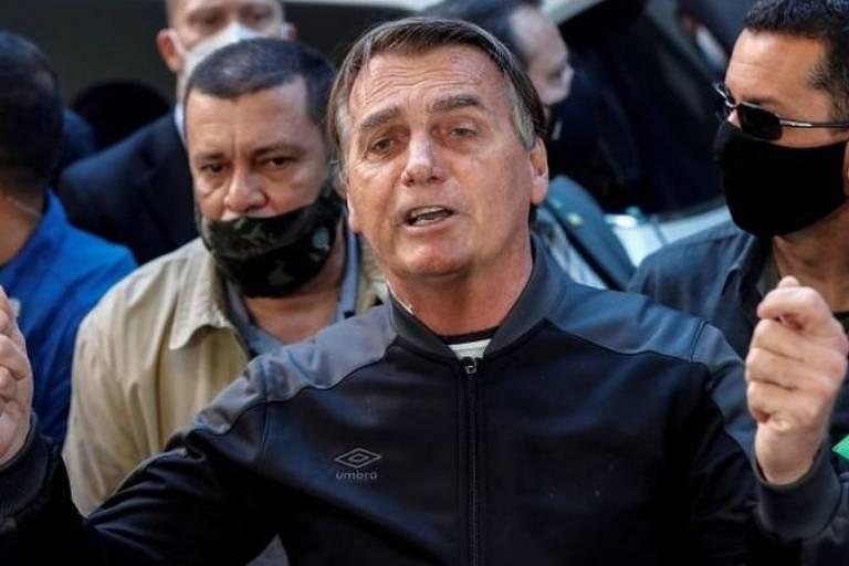 Imagem em primeiro plano mostra o presidente Jair Bolsonaro sem máscara. Ao redor dele, há pessoas de máscara.