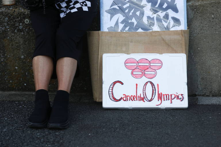 Pessoa ao lado de placa com pedido de cancelamento da Olimpíada