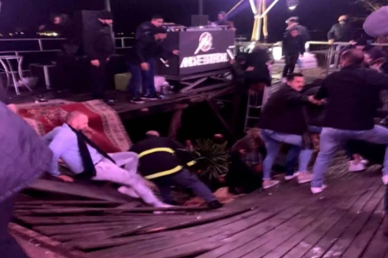 Bombeiros e pessoas em meio a deque rompido e equipamentos de festa
