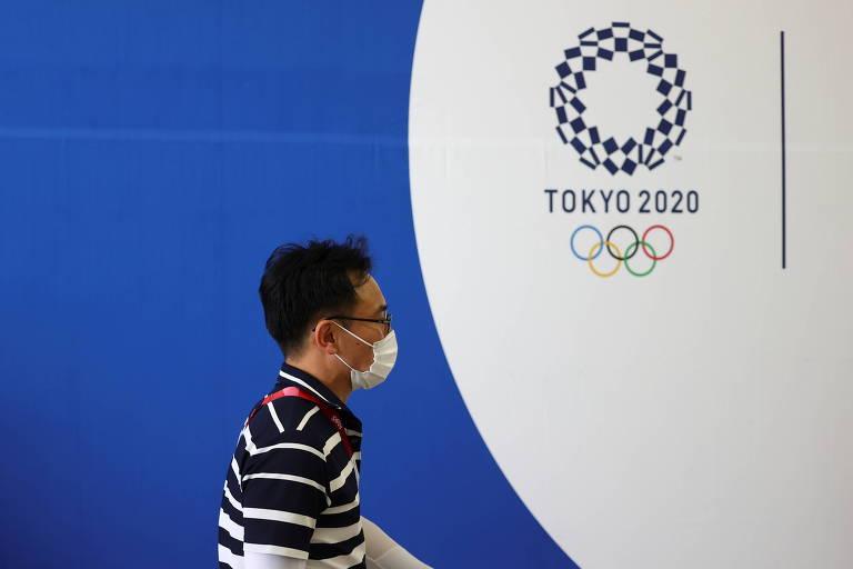 Homem com máscara em frente ao logo dos Jogos Olímpicos de Tóquio, na capital japonesa