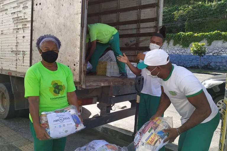 pessoas seguram cesta básica atrás de caminhão