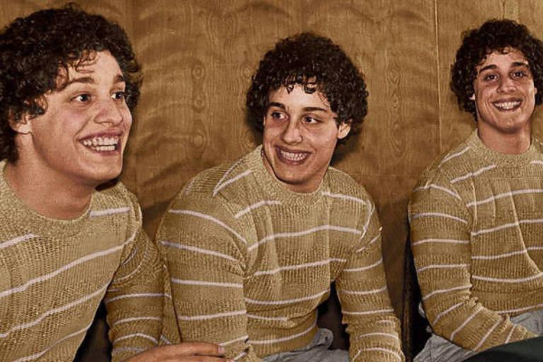 três homens de cabelo encaracolado e blusa bege sorriem lado a lado