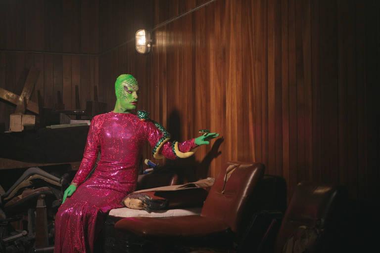 Retrato de uma drag que está pintada de verde e usa vestido rosa, e lembra uma serpente