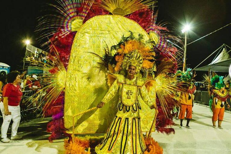 Pessoa com fantasia de carnaval amarela em desfile de escola de samba