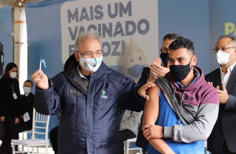 Ministro segura uma seringa com a mão direita e, com a esquerda, apoia no braço de um rapaz, que está com a manga da camisa levantada para receber a vacina