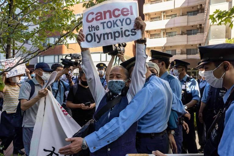 Morador mostra cartaz pedindo o cancelamento da Olimpíada de Tóquio; apesar dos protestos, Jogos estão mantidos