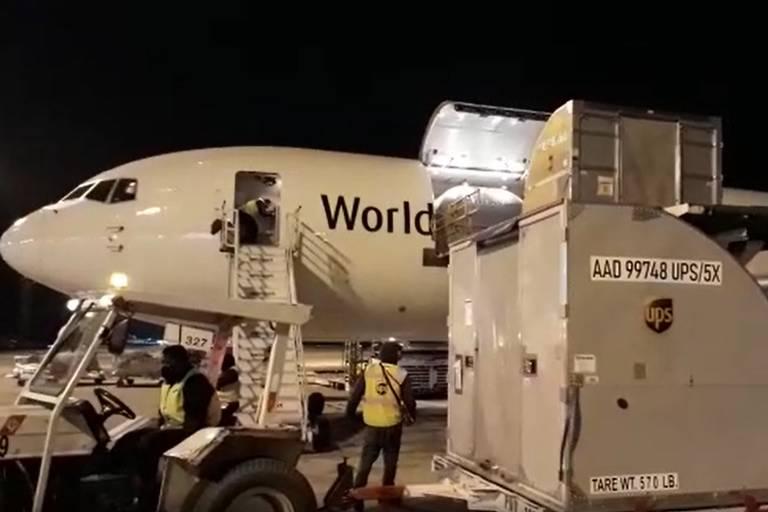 Avião e lote de vacinas sendo desembarcado