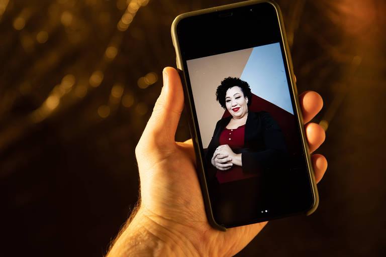 Uma mão segura um celular. Na tela, está uma foto de Maili Santos