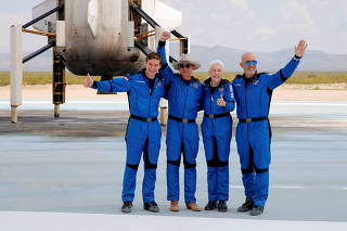 Billionaire American businessman Jeff Bezos (2nd-L) poses for pictures with crewmates, from left, Oliver Damen, 18, Bezos, Wally Funk, 82, and Mark Bezos at the landing pad after they flew on Blue Origin's inaugural flight