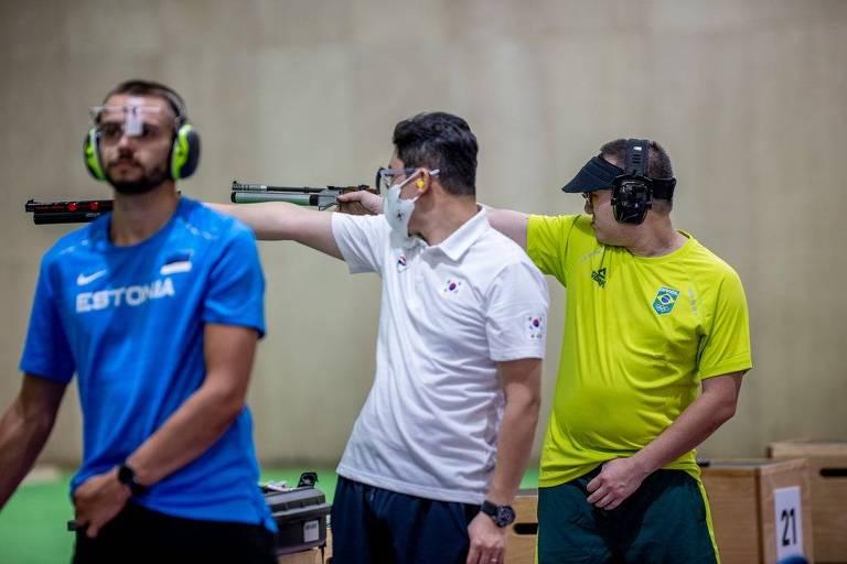 Dois atiradores miram em treino, enquanto um terceiro se prepara