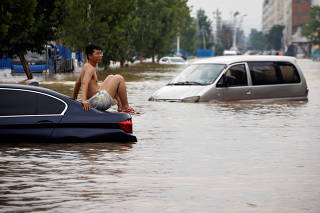 Man sits on a stranded vehicle on a flooded road following heavy rainfall in Zhengzhou