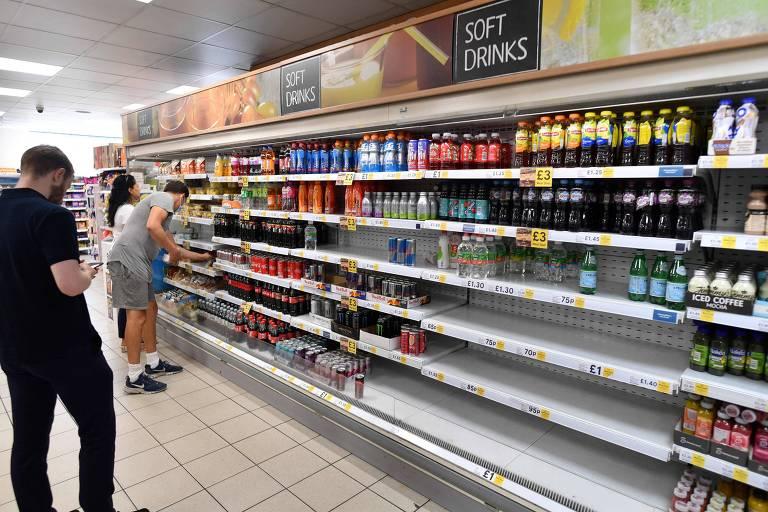 Homem de preto olha prateleira de refrigerantes com vários espaços vazios