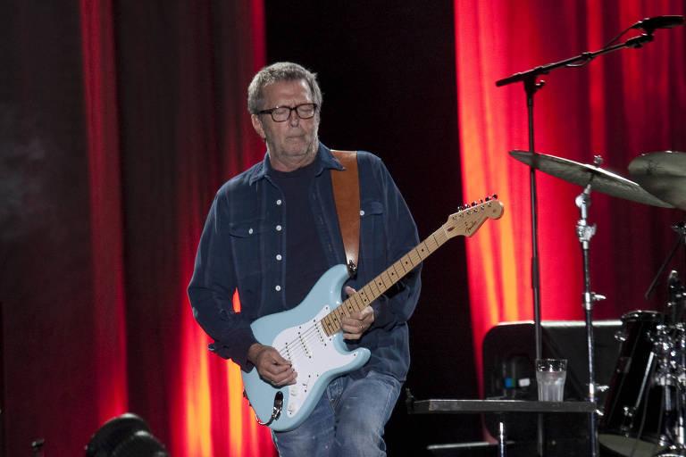 Homem branco tocando guitarra em palco