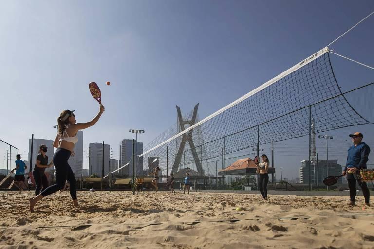 Alunos durante aula de beach tennis na escola Sampa Beach, no bairro do Morumbi; o espaço também tem quadra de vôlei de praia