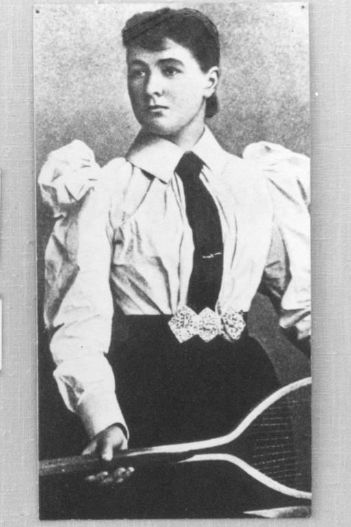 Retrato em preto e branco de tenista, que está com raquete na mão e veste camisa