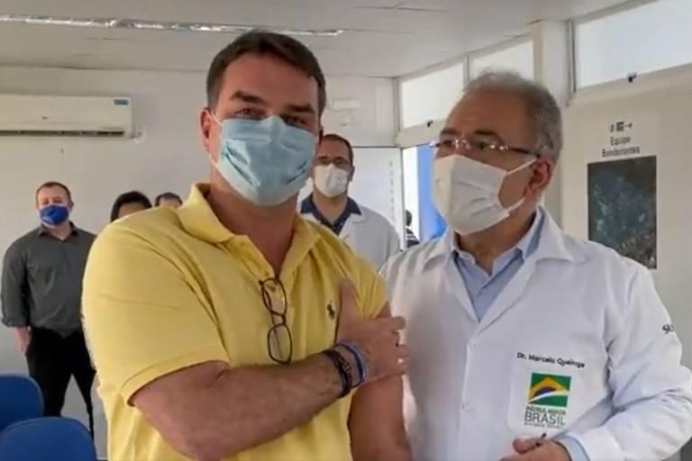 Bolsonaro seguro braço, no lugar onde foi feita a aplcação; ao seu lado está o ministro da saúde