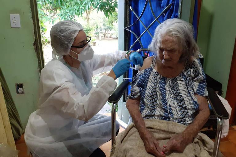 enfermeira aplica vacina em idosa sentada
