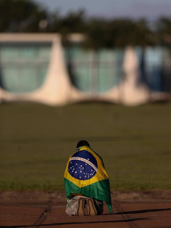 Homem envolto em bandeira do Brasil de joelho em frente ao Palácio da Alvorada