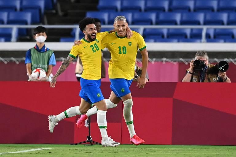 Claudinho (esq.) abraça Richarlison (dir.), que comemora o seu terceiro gol na vitória do Brasil sobre a Alemanha